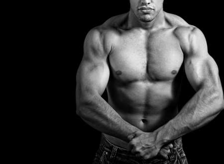 pectorals: Big athletic man showing his muscles over black background