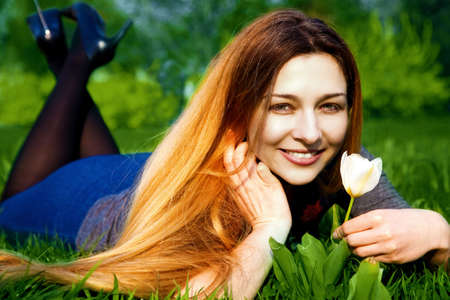 Portrait of happy young woman with tulip in fresh grass photo
