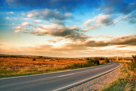 View of rural road and blue cloudy sky photo