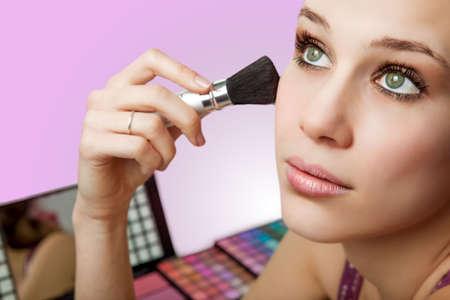 Makeup and cosmetics - beautiful woman using blush brush Stock Photo