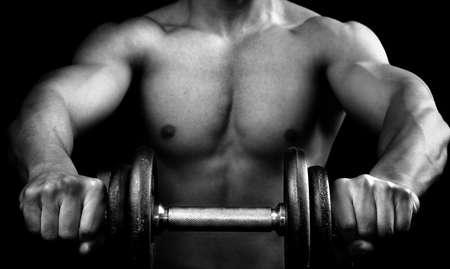 levantando pesas: Potente chico muscular, sosteniendo un mancuernas Foto de archivo