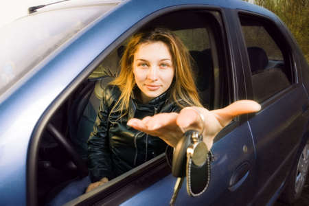 Cute woman offering keys to new car Stock Photo - 6604496