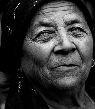 serene people: Dark artistic portrait of expressive senior lady Stock Photo