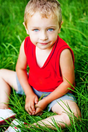 Portrait of cute serene kid on fresh green grass Stock Photo - 6604517