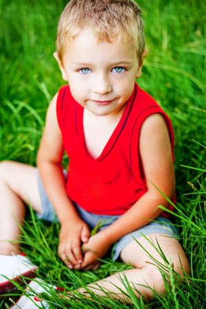 Portrait of cute serene kid on fresh green grass Stock Photo - 6604517