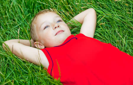 Pensive kid day dreaming in fresh grass photo