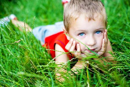 Cute blond boy relaxing on green fresh grass photo