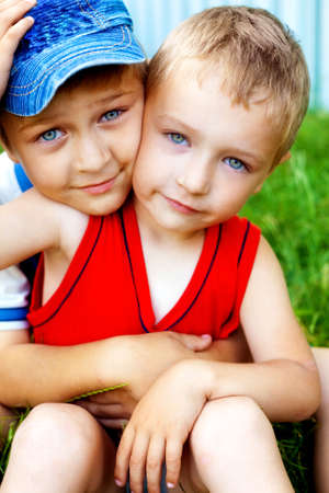 Hug of two cute loving brothers outdoors photo