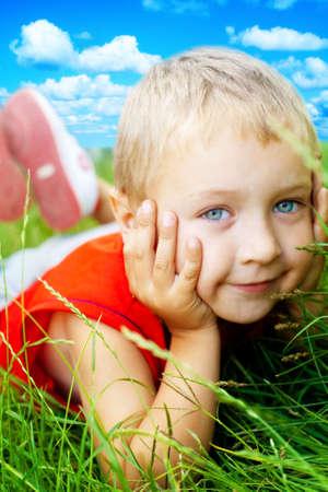 Portrait of happy cute child in the grass photo