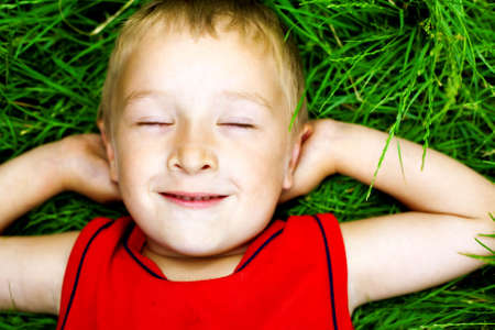 Happy dreaming child on fresh green grass photo