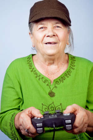 playstation: Happy senior woman playing video games with gamepad