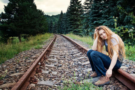 mood moody: Sad suicidal lonely young woman on railway track