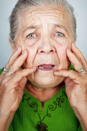 Portrait of scared and worried senior wrinkled lady photo