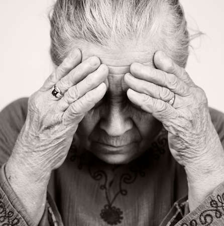 Unhappy old senior woman with health problems photo