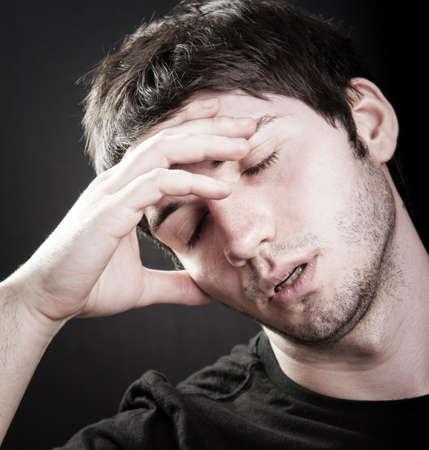 Depression concept - sad young man over black Foto de archivo