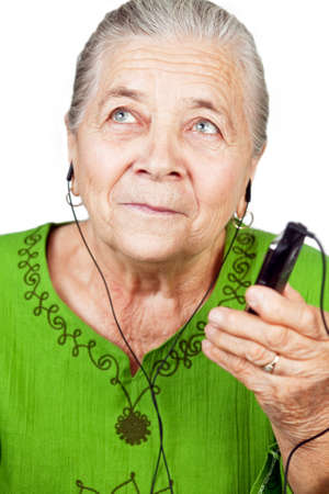 Senior old woman listening music at mobile phone photo