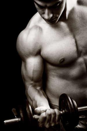 culturista: Concepto de gimnasio y fitness - fisicoculturista y dumbbell sobre negro
