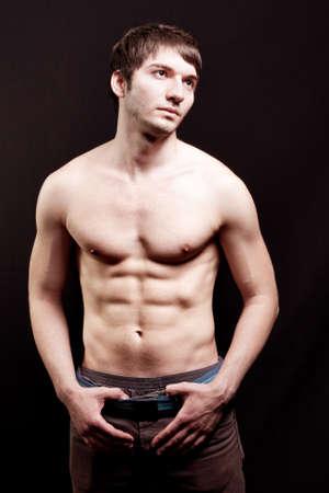 nackte brust: Shirtless jungen Kerl mit sexy abs �ber schwarz  Lizenzfreie Bilder