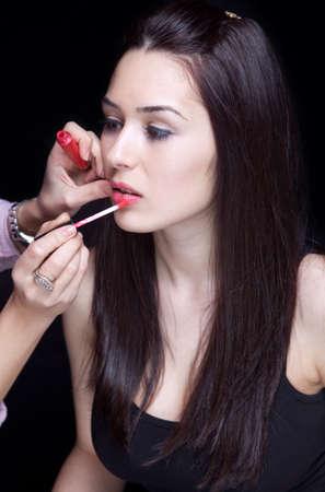 artist's model: Make-up artist applying gloss on model lips