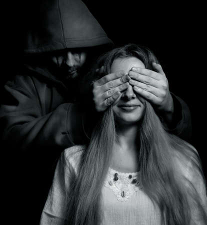 covering the face: Halloween surprise - evil man behind innocent naive girl