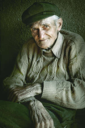 Artistic portrait of old senior man with wrinkled hands Stock Photo