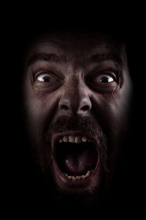 Rostro asustado de escalofriante hombre en la oscuridad
