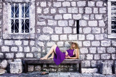 Fashion shot of elegant cute woman near stone wall photo