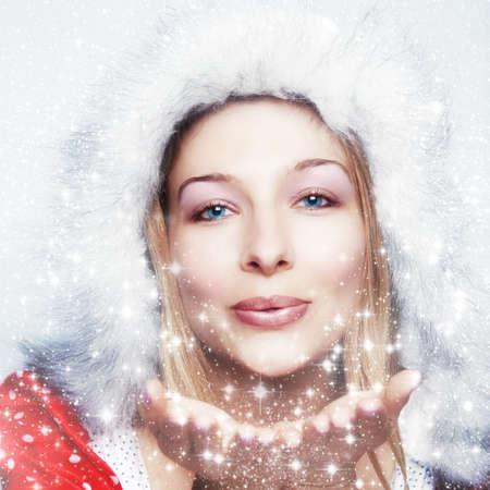 blow kiss: Happy friendly woman blowing snowflakes in winter season Stock Photo