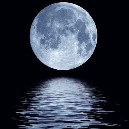 Full blue moon over cold night water  写真素材