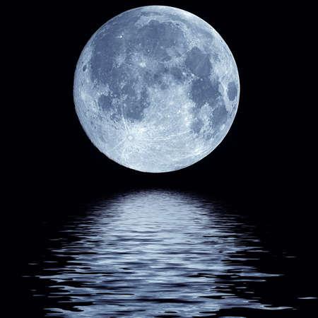 Full blue moon over cold night water  Foto de archivo