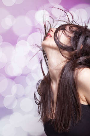 flying hair: Dancing young brunette woman with hair in motion Stock Photo