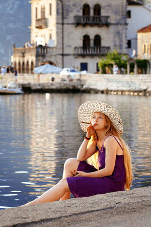 Beautiful woman relaxing by the sea in Perast, Montenegro photo
