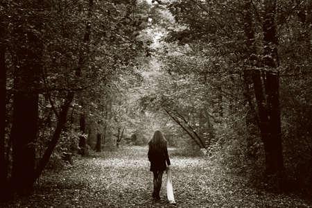 walking alone: Concepto de soledad - mujer triste solitaria en el bosque Foto de archivo