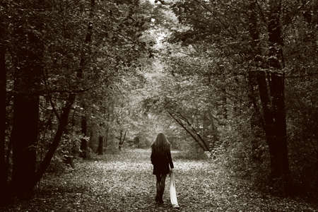 Solitude concept - lonely sad woman in the woods Stock Photo