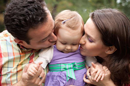 Kiss of love - happy parents with their cute baby girl