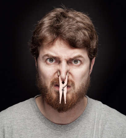 Bad smell concept - peg on male nostrils over black Stock Photo - 8880583