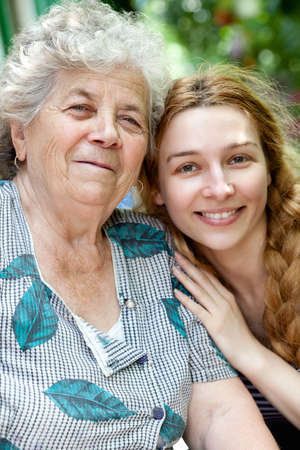 granddaughters: Family portrait of joyful young woman and her grandmother