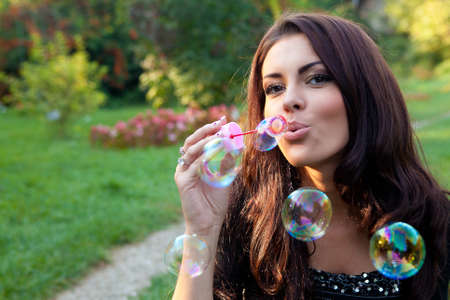 blowing bubbles: Happy carefree young woman blowing soap bubbles