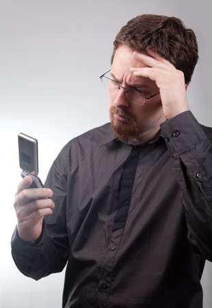 Businessman receiving bad news via mobile phone photo