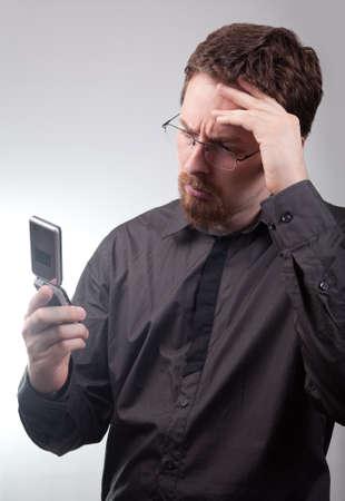 Businessman receiving bad news via mobile phone photo