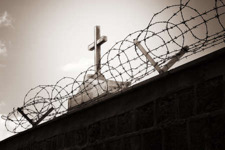 Religion and war concept - cross behind barbed wire photo