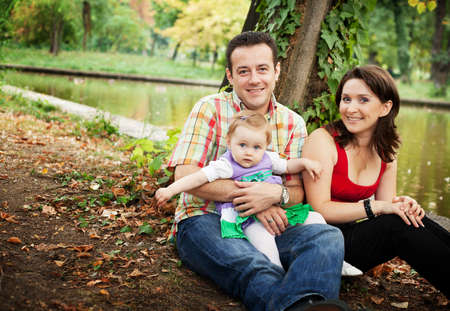 Family portrait - mother father and baby daughter outdoor photo