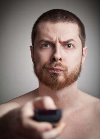 command button: Zapping concept - annoyed man with tv remote control Stock Photo