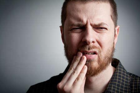 mal di denti: Mal di denti - sofferenza giovane con problemi di denti Archivio Fotografico