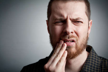 mouth pain: Toothache - suffering young man with teeth problems Stock Photo
