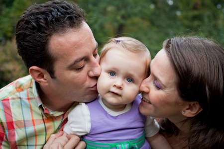 Family love - parents kiss for cute little daughter photo