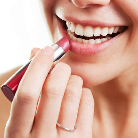 Lipstick and happy female lips over white Stock Photo - 9413699