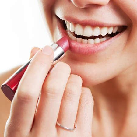 Lipstick and happy female lips over white photo