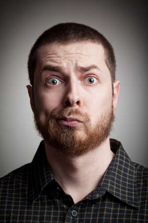 expression facial: Face of funny amazed guy isolated on gray background