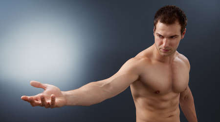 mystery man: Light and power concept - creative muscular man holding bright sphere